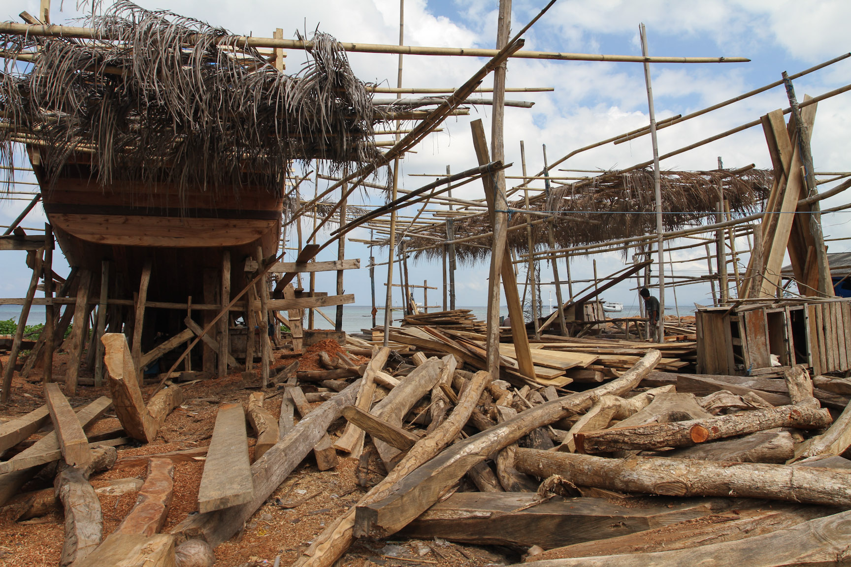 The pinisi boats are constructed right on the beach in Tanah Biru, the wood ready for use.