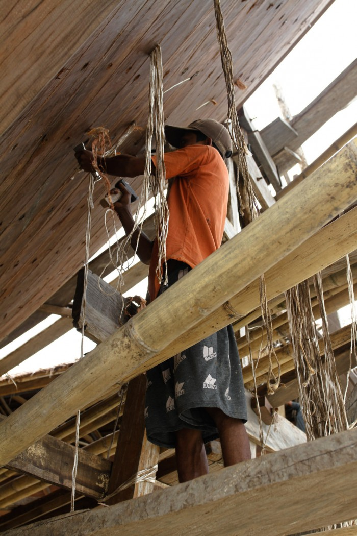 A worker knocking rope and bark between the planks to prevent leaking once it hits the water.
